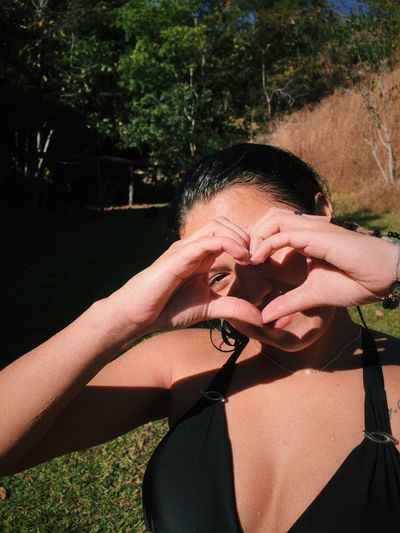 Portrait of woman making heart shape with hands over face against trees