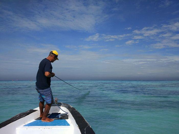 Full Length Of Man Fishing In Sea Against Sky