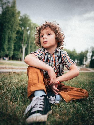 Boy looking away while sitting on field