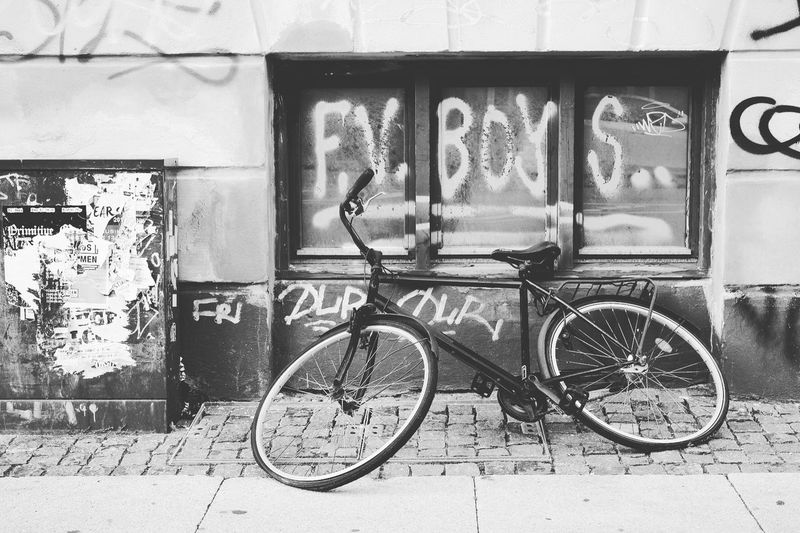 Bicycle parked against wall in city
