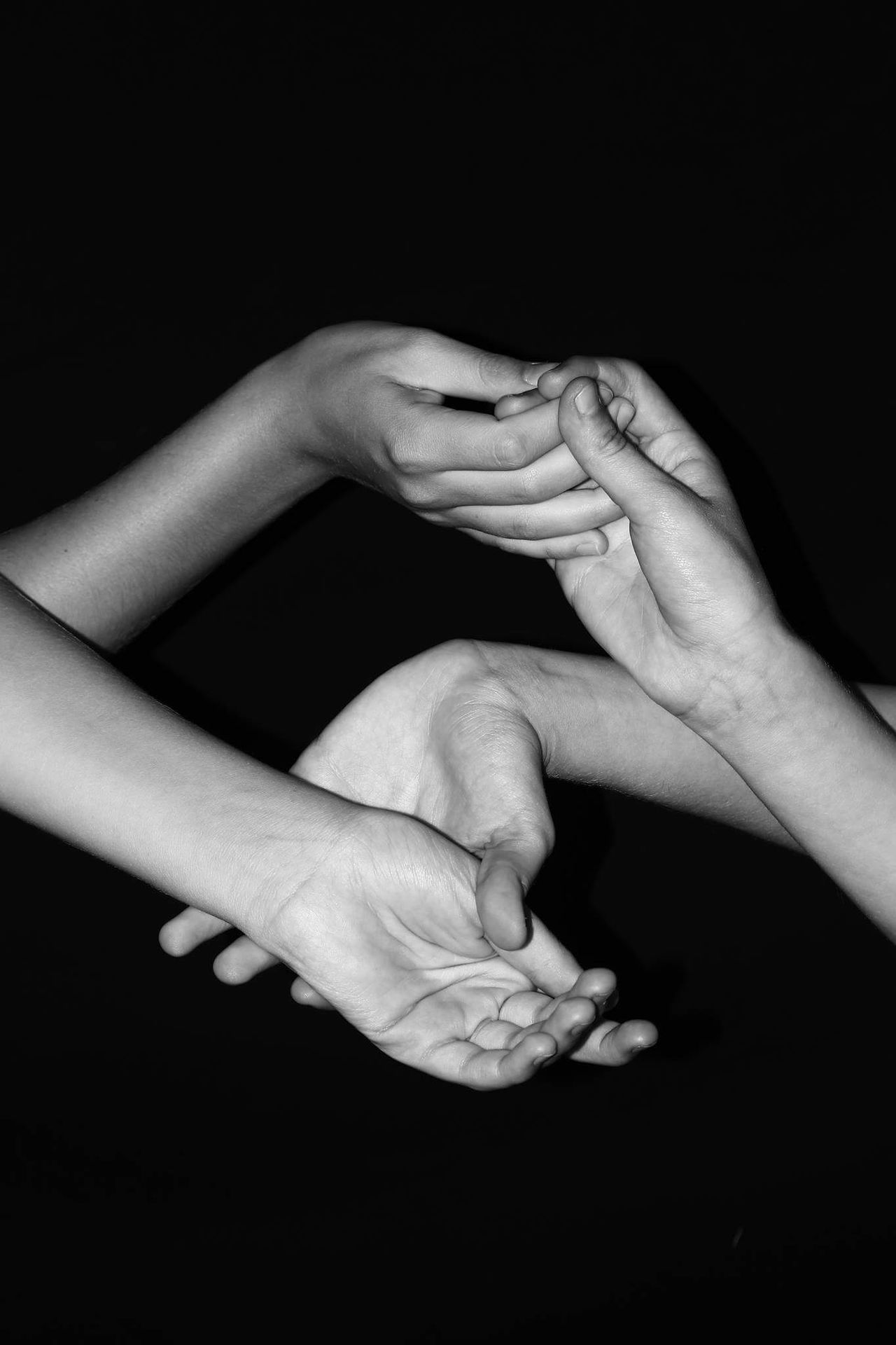 Cropped hands of people against black background