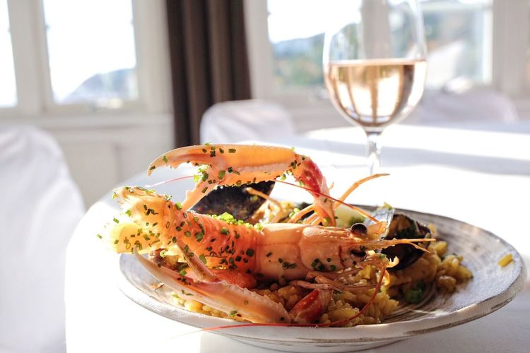 Scampi served with wineglass on table at restaurant