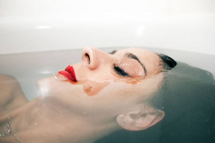 Midsection of woman with chocolate face in bathtub
