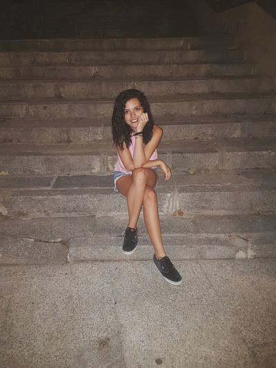 Portrait of smiling beautiful woman sitting on steps at night