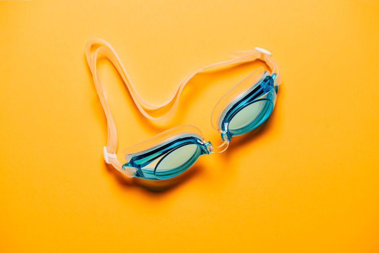 High angle view of paper with swimming goggles on table