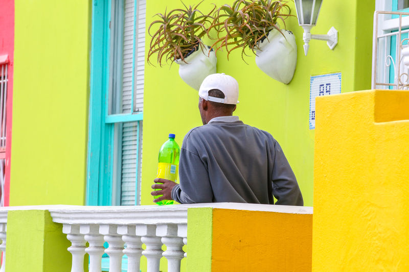 Man standing with a bottle on a balcony Balcony Balustrade Bo-kaap Building Exterior Color Man Rear View