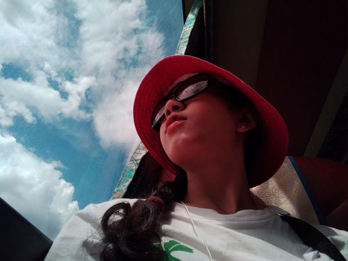 Low angle view of woman wearing sunglasses and hat against cloudy sky