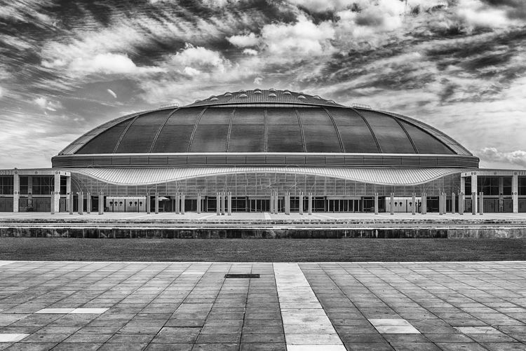BARCELONA - AUGUST 11: Palau Sant Jordi (English: St. George's Palace) is an indoor sporting arena in the Olympic Ring complex on Montjuic hill, Barcelona, Catalonia, Spain, as seen on August 11, 2017 Built Structure Cloud - Sky Architecture Building Exterior Sky Nature Day No People Building Modern City Glass - Material Outdoors Reflection Travel Destinations Footpath Dome Design Flooring Tiled Floor