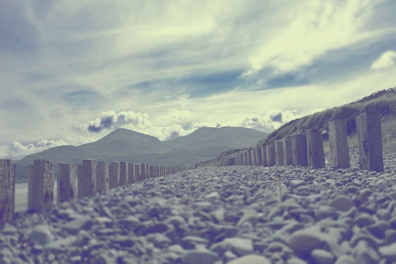 Surface level view of pebbles at beach against cloudy sky at murlough bay