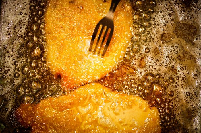 Closeup of two Milanese with a fork, Cooking frying Vegetable Oil isolated Bubbles