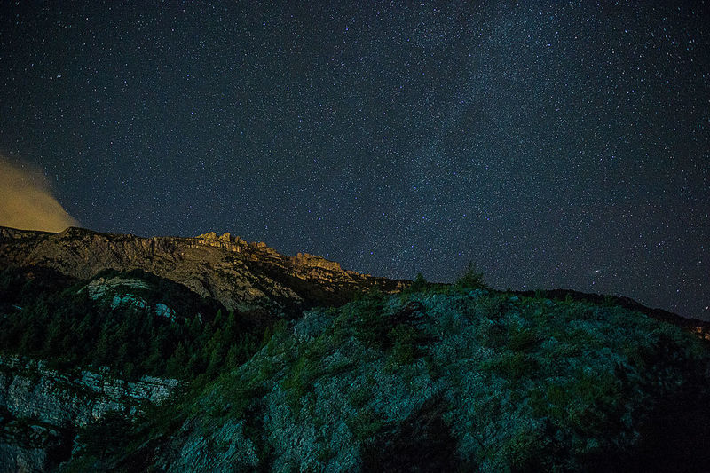 Low angle view of mountains against star field