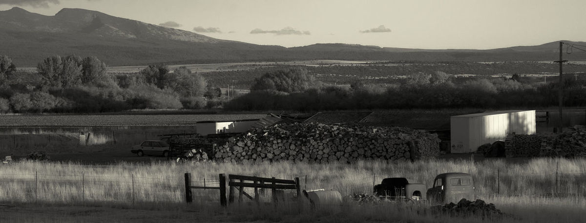 The backyard items in a rural USA backyard with mountains in the background. Americana Backyard Junk Junk Cars Relaxing Black And White Day Landscape Mountain Nature No People Outdoors Scenics Sky Tree