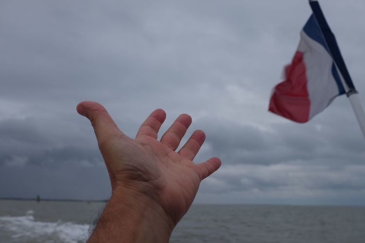 Cropped hand by french flag at sea9