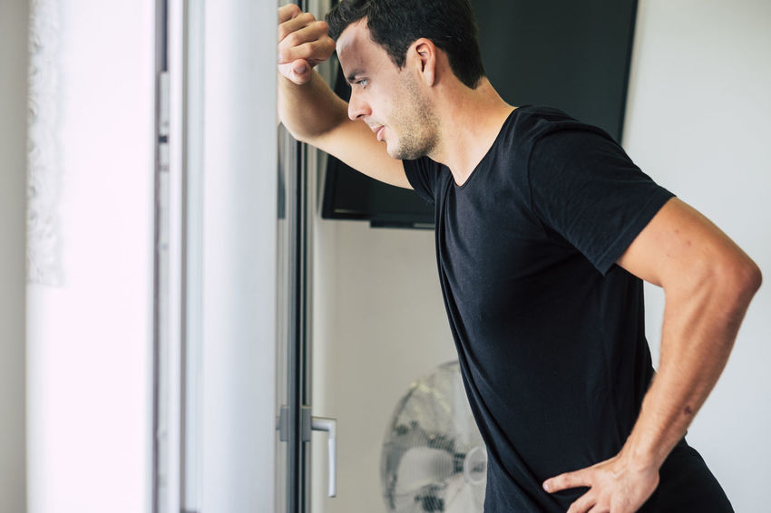 beautiful modern fashion young man at home lose in his thoughts near the window door. light from outdoor One Person Indoors  Real People Young Adult Young Men Casual Clothing Standing Side View Lifestyles Looking Men Waist Up Black Color Three Quarter Length Beard Contemplation Occupation Home Interior Thoughtful Caucasian Black Tshirt Son 25-29 Years Window Black Hair