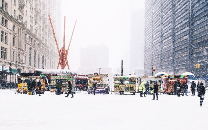 People on snow covered city against sky