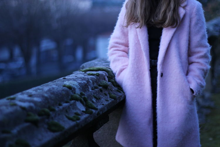 Midsection Of Woman Wearing Pink Long Coat Standing By Railing At Dusk