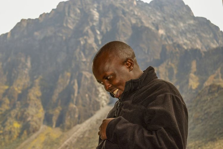 A hiker against a blurred background of mount baker, rwenzori mountains, uganda