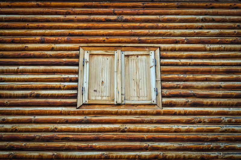 Closed window amidst wooden wall
