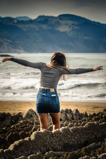 Rear view of woman with arms outstretched standing on beach