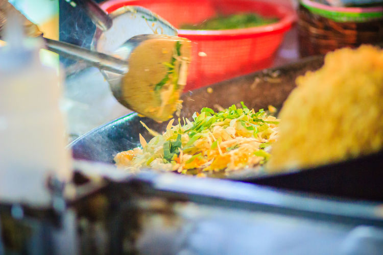 Close up hand of vendor during cooking for Padthai, the original Thai Fried Noodle, stir-fried noodle with shrimp and egg commonly served as a street food popular in Thailand Khao San Rd Khao San Road KhaoSan Khaosan Rd. Khaosandroad Khao San Khao San Knok Wua Khao San Rd. Khaosan Road Khaosanroad Night Market Night Market In Thailand Padthai