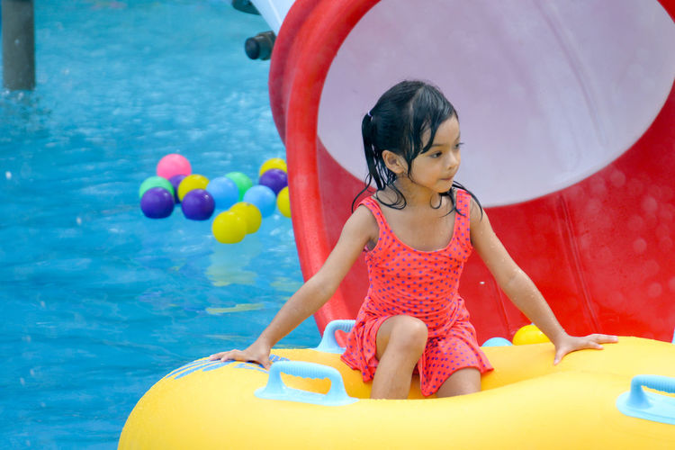 Cute girl looking away while sitting in inflatable ring on swimming pool
