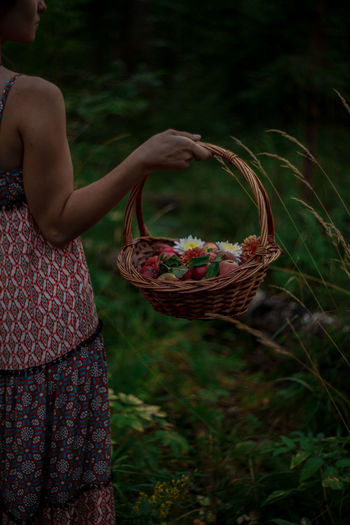 Midsection of woman holding ice cream in basket