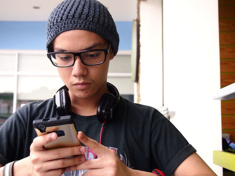 A teenager wearing eyeglasses and beanie using a smartphone Boy Call Cellphone Communication Device Fashion Gadget Hipster Internet Kid Male Online  Phone Smartphone SMS Surf Technology Teen Teenagers  Telecommunication Telephone Text Web Young Youth