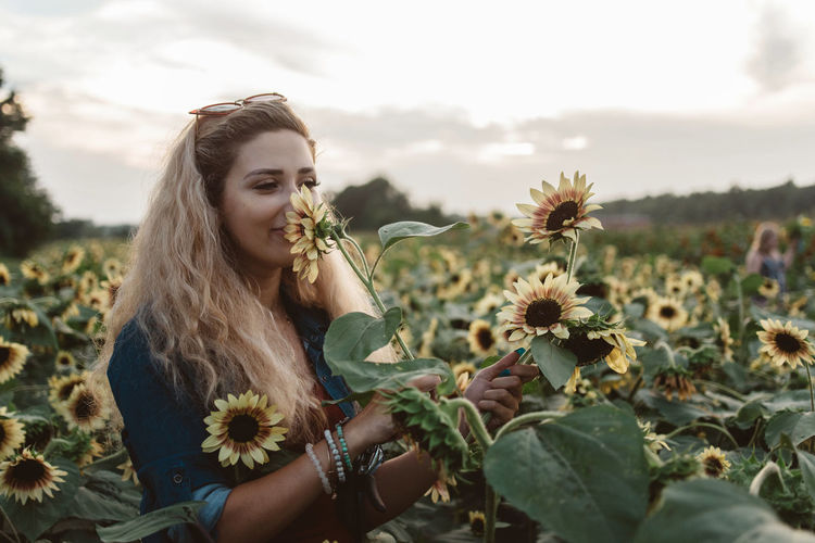 Portrait of young woman by sunflower on field