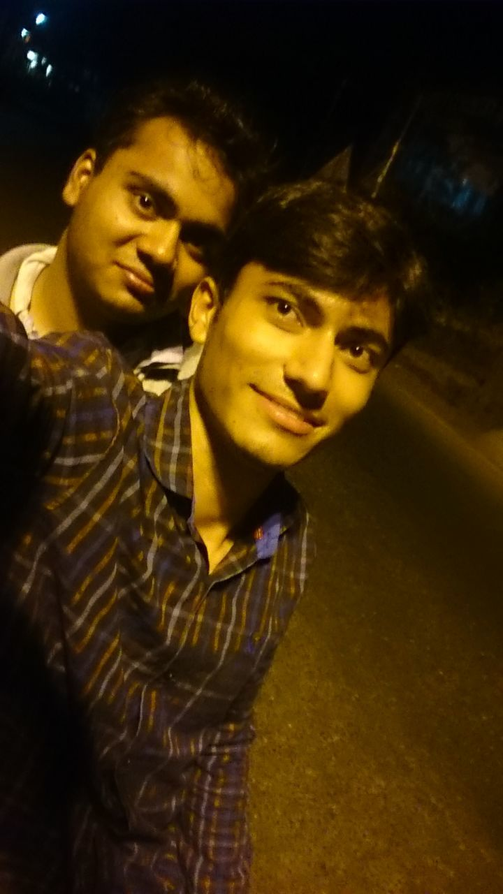 two people, looking at camera, night, portrait, real people, boys, young adult, young men, togetherness, young women, lifestyles, smiling, leisure activity, happiness, illuminated, indoors, posing, bonding, standing, friendship