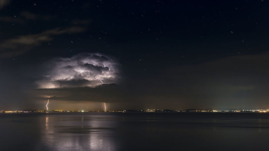 Scenic view of sea with lighting against sky at night