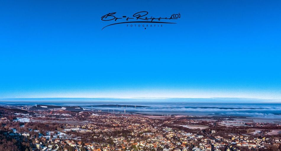 Aerial view of city by sea against clear blue sky