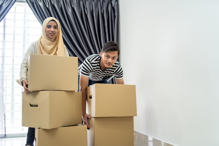 asian couple moving out and moving in into new house Adult Box Box - Container Cardboard Cardboard Box Casual Clothing Couple - Relationship Emotion Happiness Heterosexual Couple Indoors  Men Moving House People Smiling Two People Wife Women Young Adult Young Men Young Women
