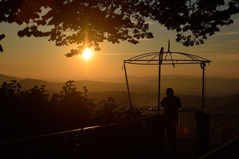 Silhouette Of Man On Balcony Looking At Landscape At Sunset