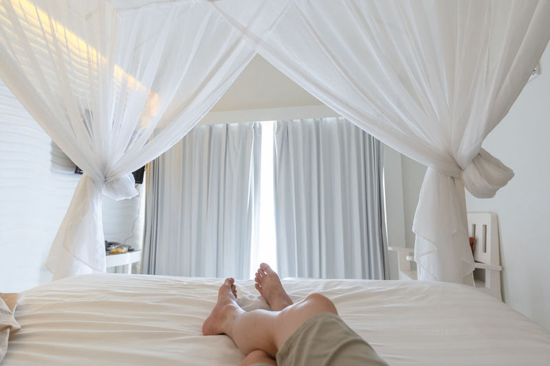 Man stretching legs in mosquito net on the bed at vacation, sunlight through curtain in bedroom