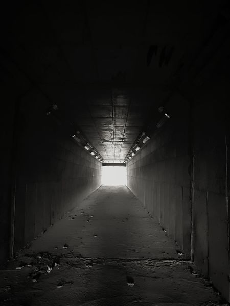 EyeEmNewHere Rear View Sillouette Black And White Rare Light And Shadow Infinity Salvation  Illuminated Tunnel Architecture The Way Forward Empty Road Pathway Road Marking Narrow Urban Scene