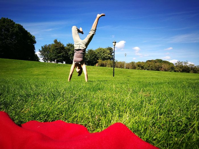 Mid adult woman doing handstand on grassy field against sky