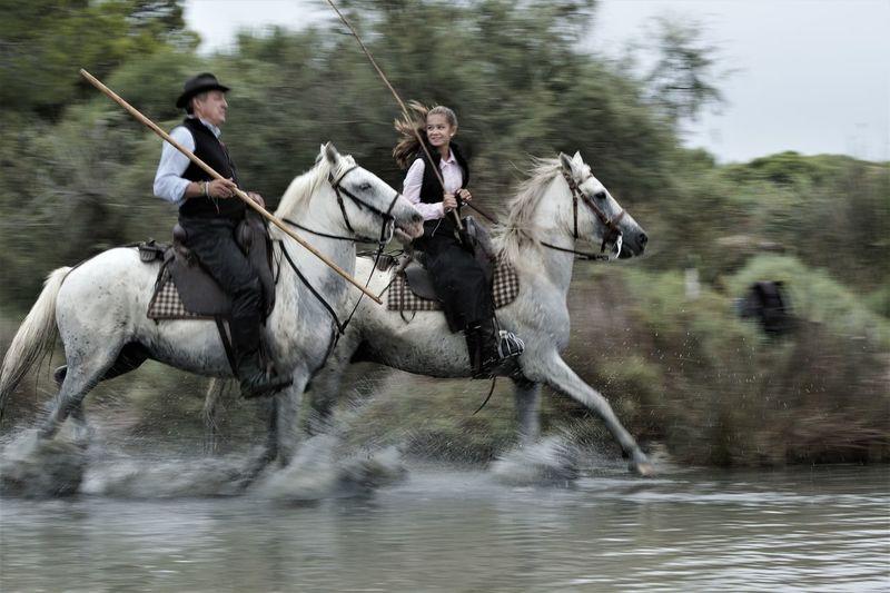 Men riding horse in lake