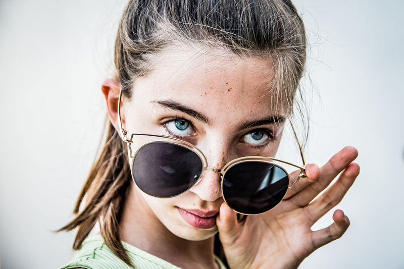 Portrait of woman with sunglasses against white background