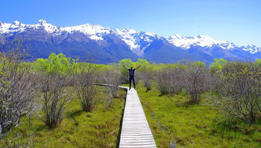 Man Raising Hands On Pathway Along Countryside Landscape