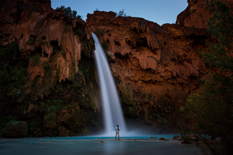 View of man standing in front of waterfall
