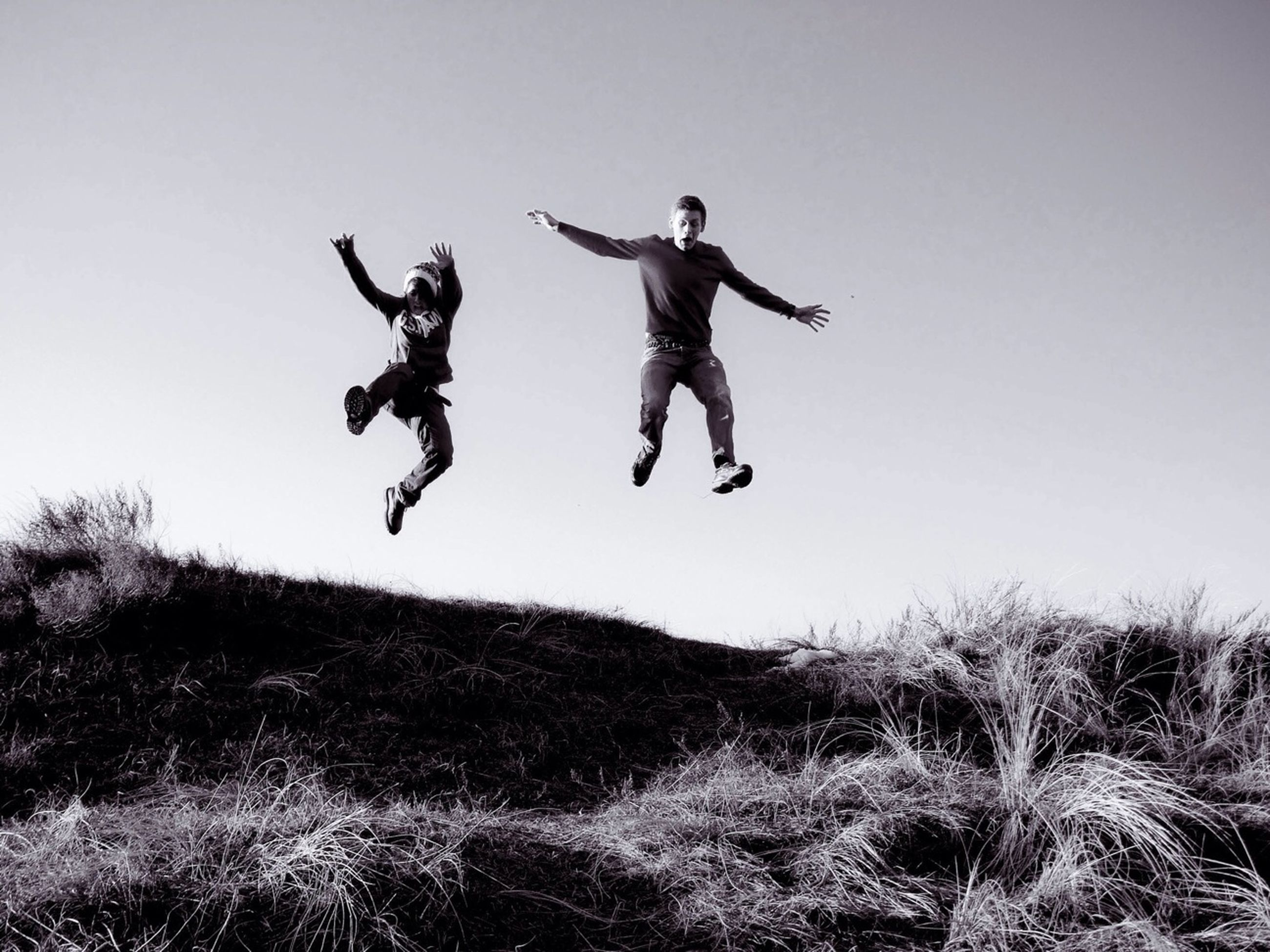 full length, mid-air, lifestyles, jumping, leisure activity, fun, enjoyment, men, freedom, sport, clear sky, arms outstretched, vitality, motion, childhood, low angle view, carefree, casual clothing