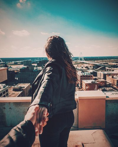 Young woman with arms raised in city against sky during sunset