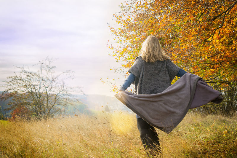 Woman in autumn scenery dances with a cover Cardigan Fashion Atmospheric Autumn Autumn Scenery Blond Hair Comfortable Clothes Cord Clothes Cover Dances Deciduous Forest High Boots Joy Lens Flares Lifestyles Movement Nature Poncho Rotation Sheets Skirt Turns Warm Clothes Warm Colours Women