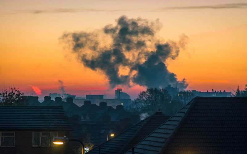Smoke emitting from city against sky during sunset