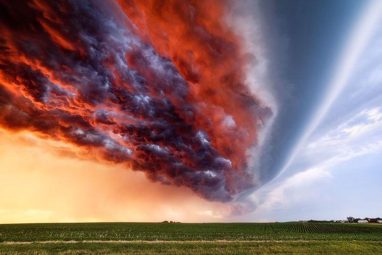 Sunset illuminates a turbulent sky beneath a shelf cloud ahead of an advancing storm.