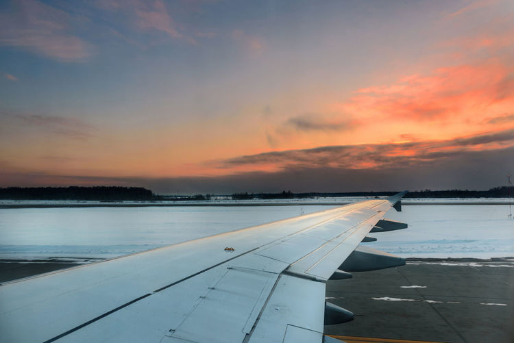 View from inside an airplane taxiing before a winter evening departure. The wing is not yet configured for takeoff Runway Travel Travel Photography Traveling Travelling Winter Air Vehicle Airliner Airplane Airplane Wing Airport Aviation Cloud - Sky Departure From Inside No People Sunset Taxiing Transportation