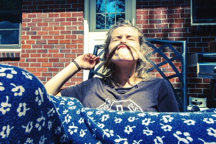 young woman fooling around Casual Clothing Fun Time Young Woman Young Woman Smiling Young Adult Funny Face Funny Faces Goofing Around Fooling Around Backyard Moustache Balcony Front View One Person Smiling Real People Portrait Lifestyles Happiness Outdoors