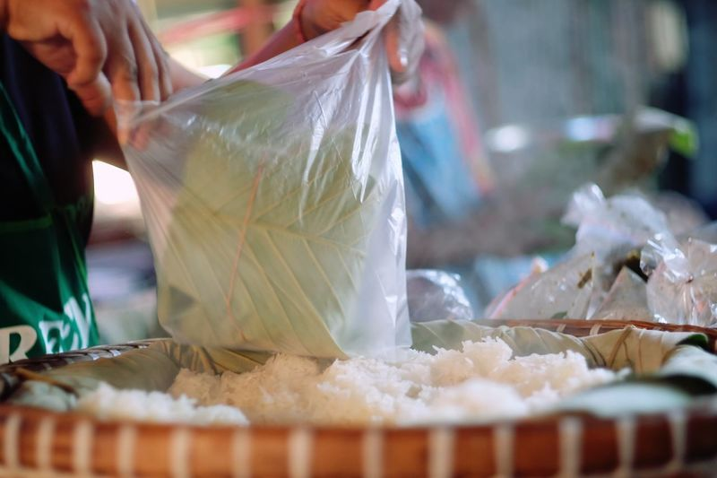 Cropped Hand Of Person Holding Food In Plastic Bag At Market