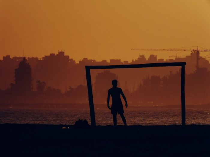 Silhouette man standing at beach by goal post against clear sky during sunset