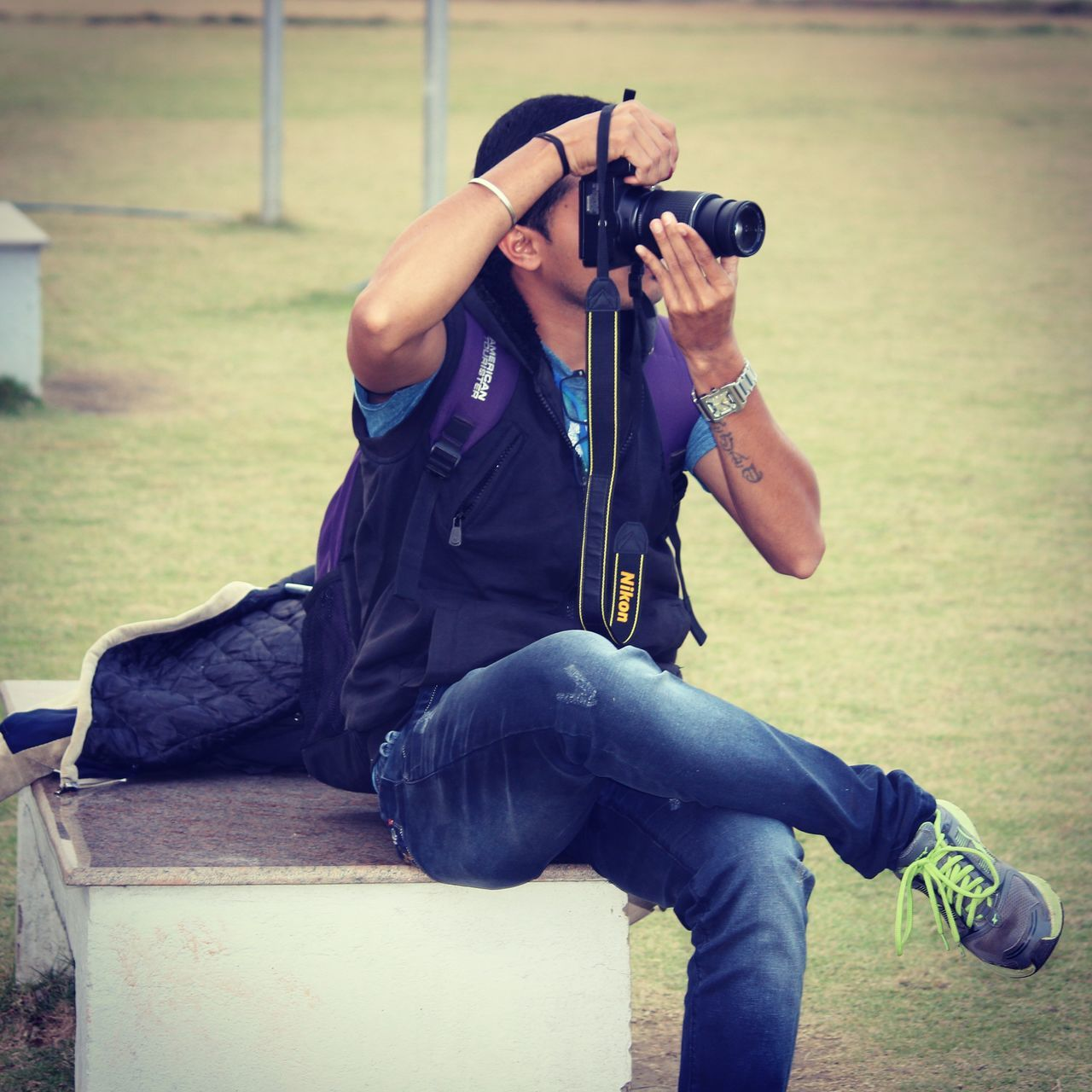 real people, sitting, photographing, holding, camera - photographic equipment, one person, photography themes, photographer, leisure activity, grass, casual clothing, day, outdoors, technology, camera, men, full length, slr camera, one man only, digital single-lens reflex camera, adult, people